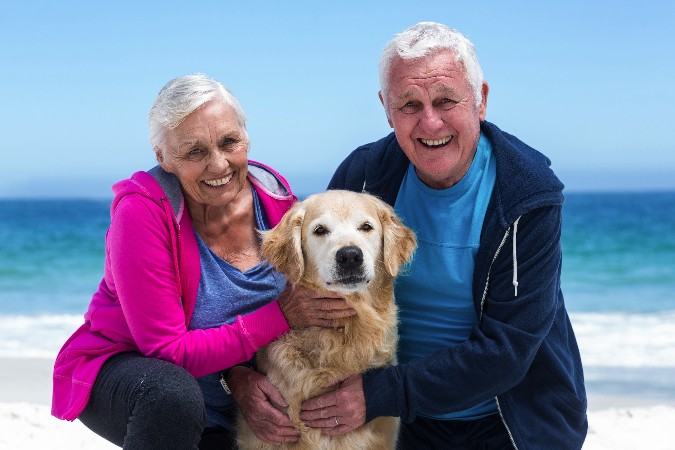 Older Couple on Beach with Dog